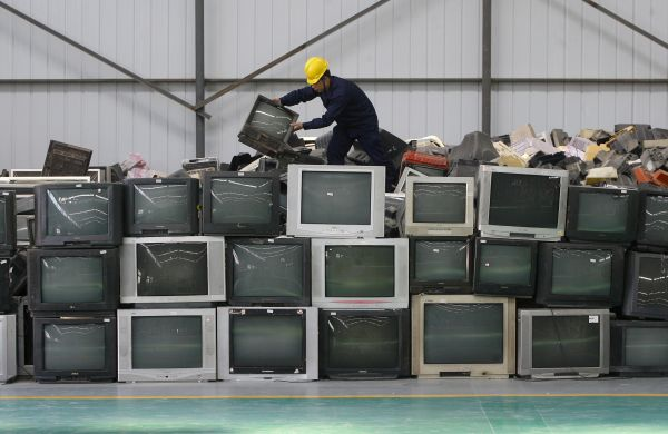 An employee arranges discarded televisions at a newly opened electronic waste recycling factory in Wuhan