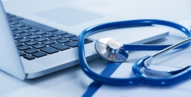 Close Up Of Laptop And Stethoscope On Desk
