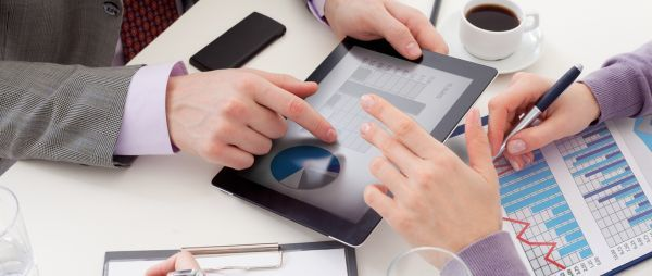 Unrecognizable business colleagues working together and using a digital tablet