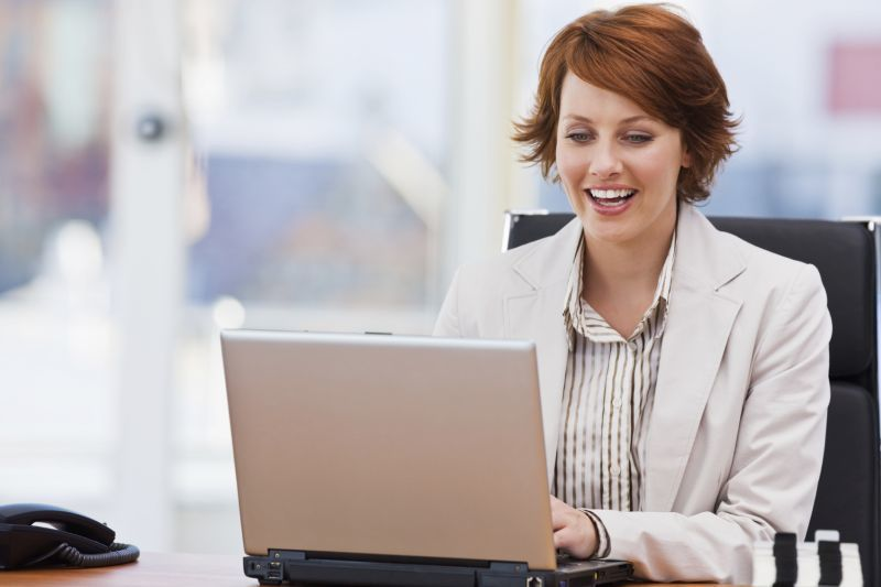 Happy young businesswoman working on laptop sitting on chair